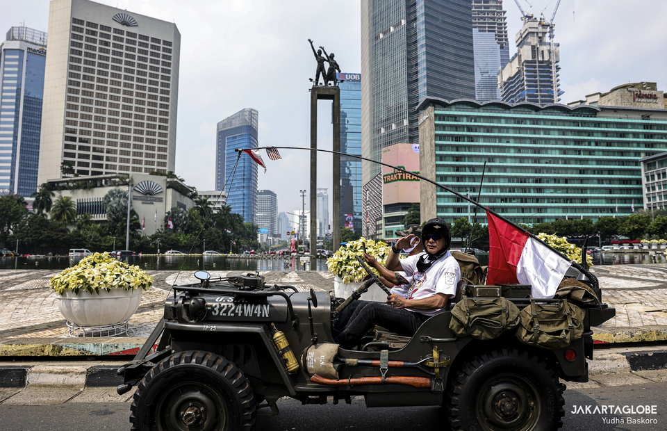 A man rides military car as he gives salute to Indonesian flag during moment of silence in Hotel Indonesia roundabout at Central Jakarta on Monday (17/08). (JG Photo/Yudha Baskoro)