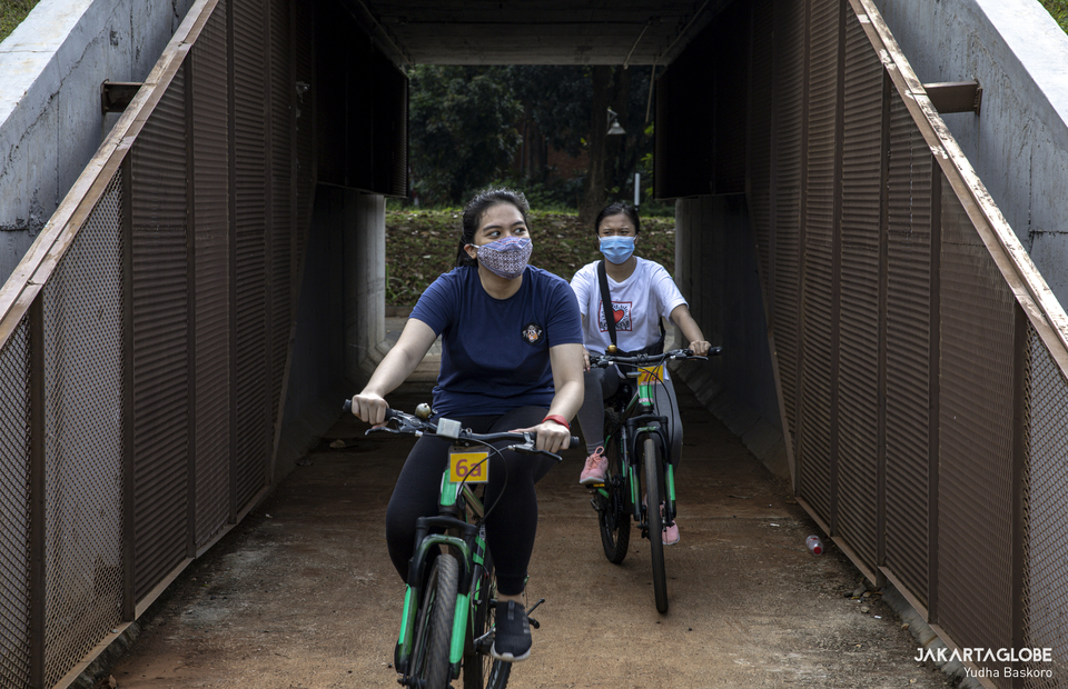 Two woman ride their bicycle at Hutan Kota GBK inside Gelora Bung Karno Sport Complex at Central Jakarta on Friday (21/08). (JG Photo/Yudha Baskoro)