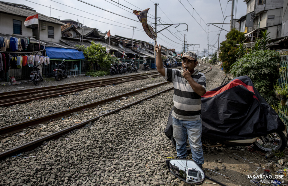 A man waves a flag as a train passes at a rail way in Kampung Grogol, Central Jakarta on Monday (24/08). (JG Photo/Yudha Baskoro)