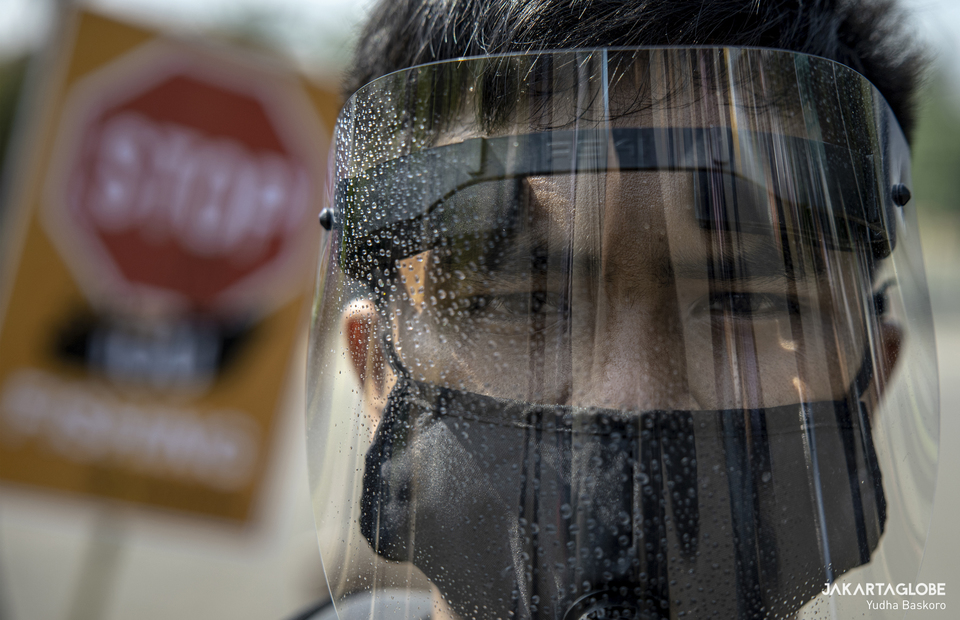 A man wearing mask and face shield as he protests at Aspiration Park in front of National Monument, Central Jakarta on Thursday (27/08). (JG Photo/Yudha Baskoro)