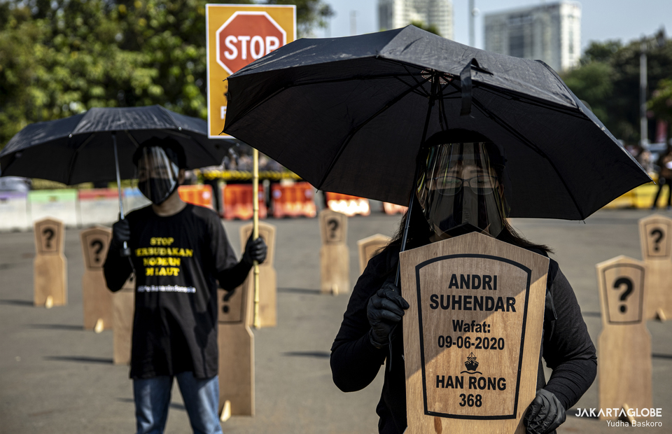 A protester carry a headstone that reads a name of Indonesian crew who died on Chinese fishing vessel during protest at Aspiration Park in front of National Monument, Central Jakarta on Thursday (27/08). (JG Photo/Yudha Baskoro)