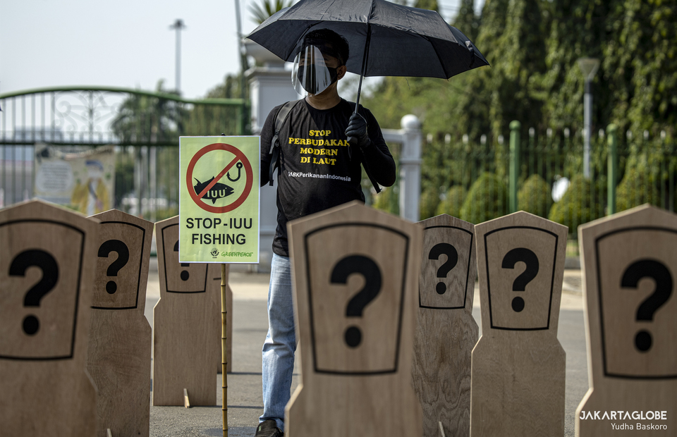 A protesters carries a placard that reads stop Illegal, unreported and unregulated fishing in Indonesia during protest at Aspiration Park in front of National Monument, Central Jakarta on Thursday (27/08). (JG Photo/Yudha Baskoro)