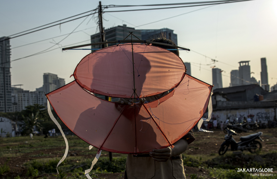 A child carries a kite at Menteng Atas, South Jakarta on Thursday (28/08). (JG Photo/Yudha Baskoro)