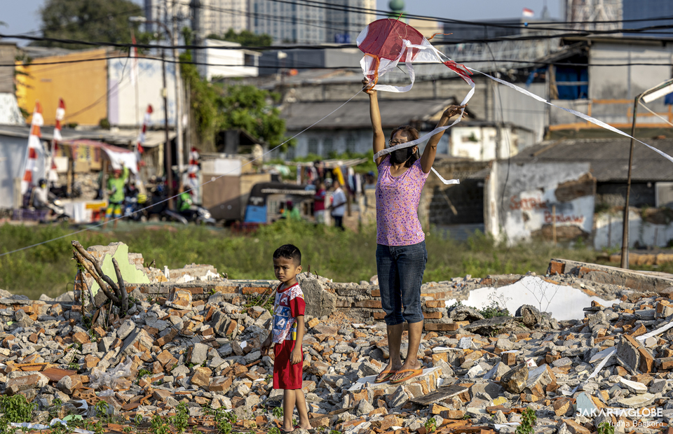 A mother teaches her child how to fly a kite at Menteng Atas, South Jakarta on Thursday (28/08). (JG Photo/Yudha Baskoro)