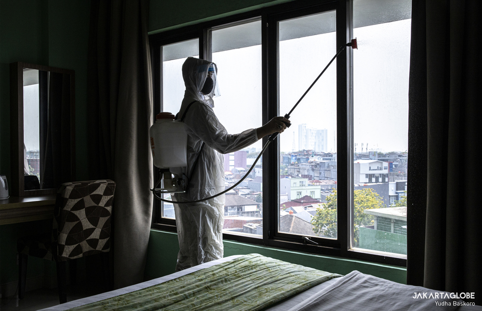 A hotel staff wearing protective gear sprays disinfectant to a hotel room inside Green Hotel in Bekasi, West Java on Thursday (24/09). (JG Photo/Yudha Baskoro)
