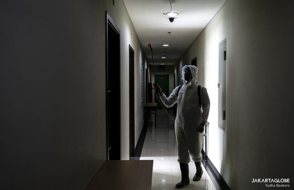 A hotel staff wearing protective gear sprays a hotel room with disinfectant in Green Hotel, Bekasi, West Java on Thursday (24/09). (JG Photo/Yudha Baskoro)