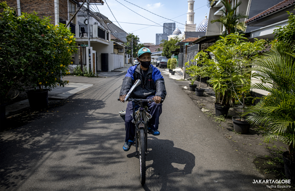 Suyoto, wearing mask, delivers a newspaper in Tebet, South Jakarta. (JG Photo/Yudha Baskoro)