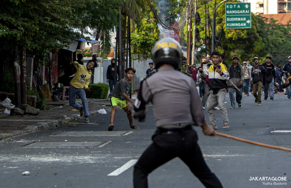 A police personnel using a bamboo stick to fight the rioters in Jalan Pejompongan Raya, Palmerah, West Jakarta on (07/10). (JG Photo/Yudha Baskoro)