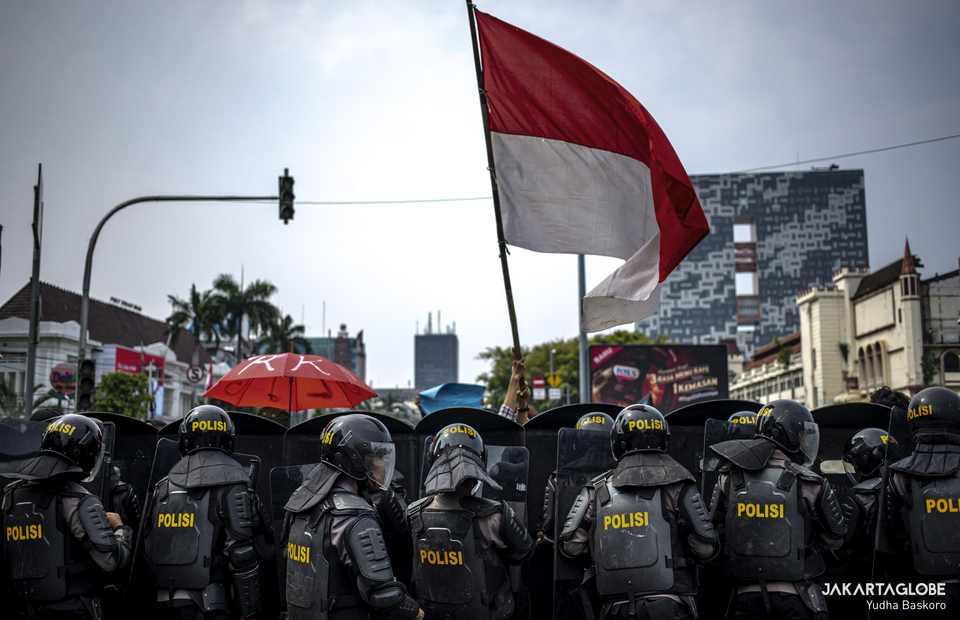 A protester is waving Indonesian flag during riot in Harmoni, Central Jakarta on Thursday (08/10). (JG Photo/Yudha Baskoro)