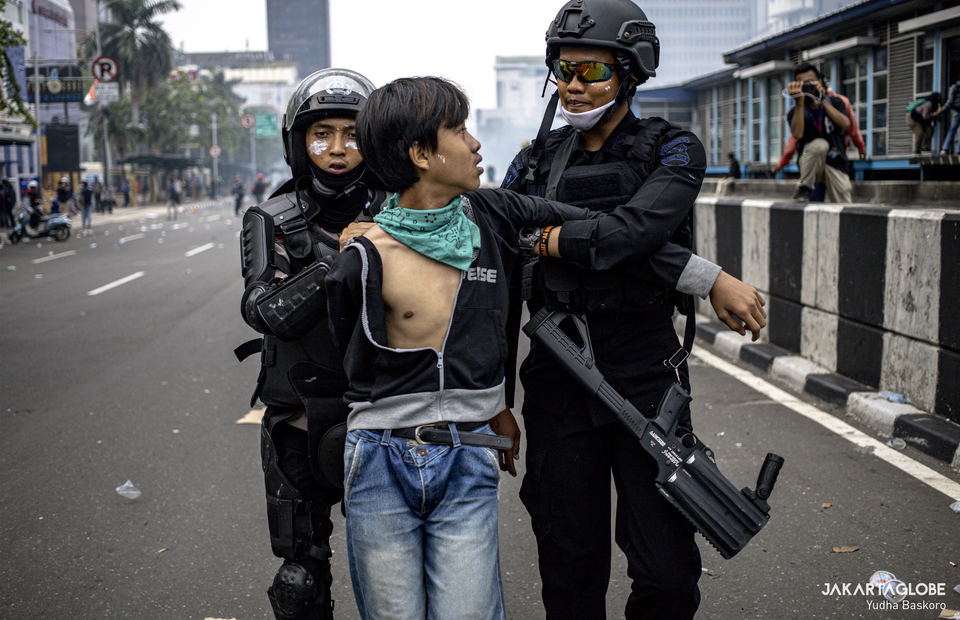 Police personnels detained a protester during riot in Harmoni, Central Jakarta on Thursday (08/10). (JG Photo/Yudha Baskoro)