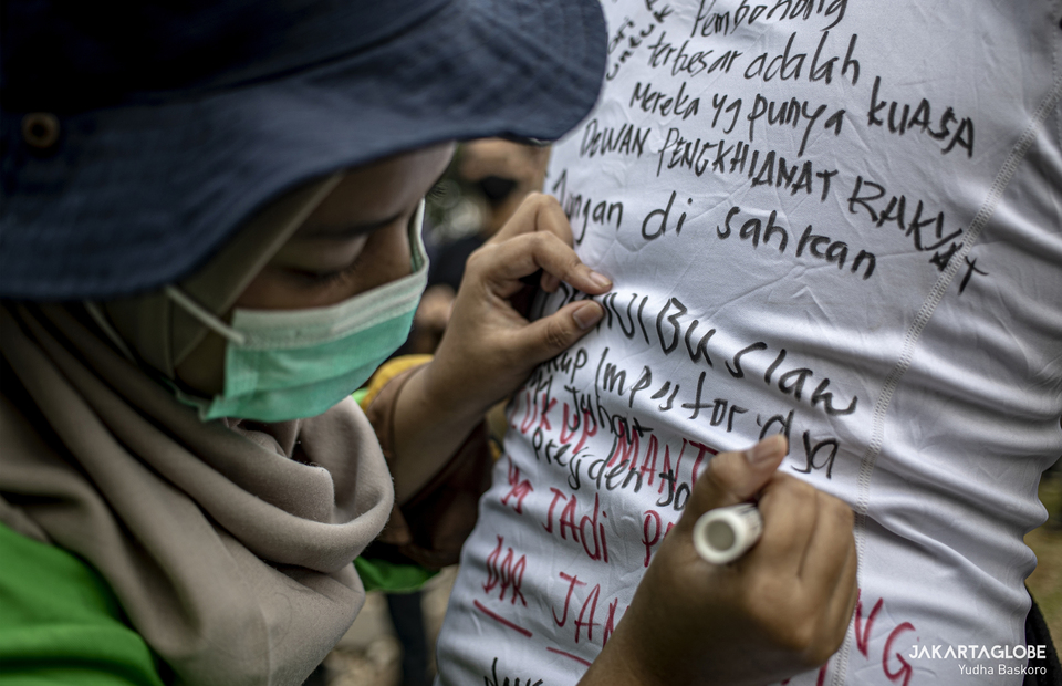 A protester writes some demands for the goverment during protest in Arjuna Wiwaha Horse Statue in Central Jakarta on Friday (16/10). (JG Photo/Yudha Baskoro)