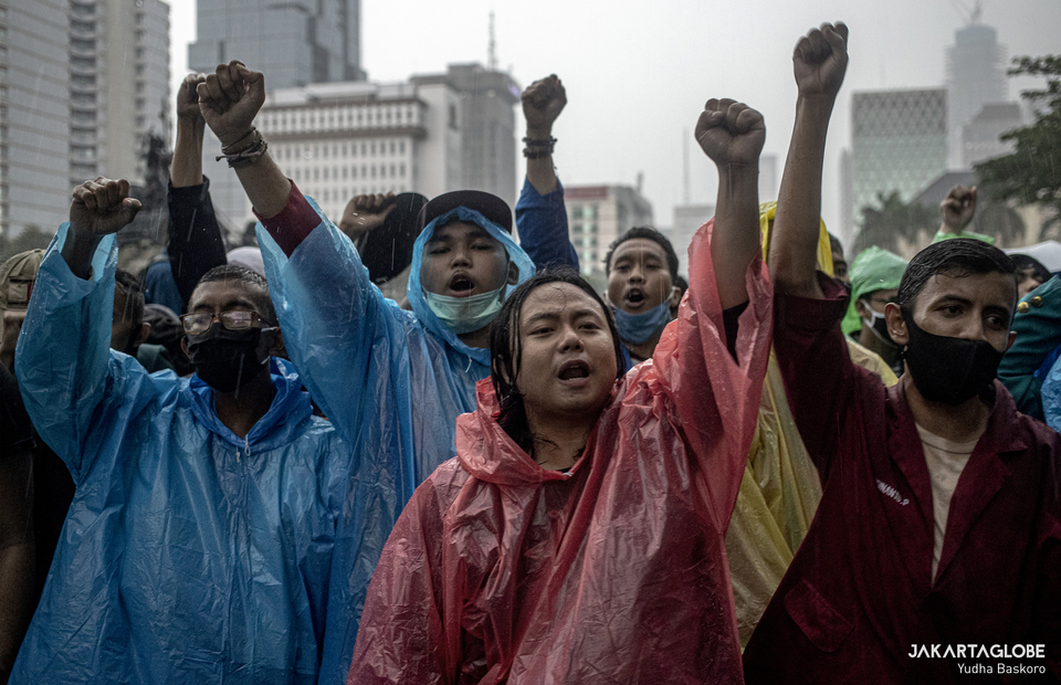 Protesters wearing plastic raincoat protest in Arjuna Wiwaha Horse Statue in Central Jakarta on Friday (16/10). (JG Photo/Yudha Baskoro)