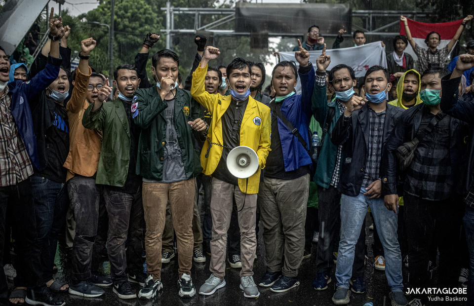 University students protest under the heavy rains in Arjuna Wiwaha Horse Statue in Central Jakarta on Friday (16/10). (JG Photo/Yudha Baskoro)