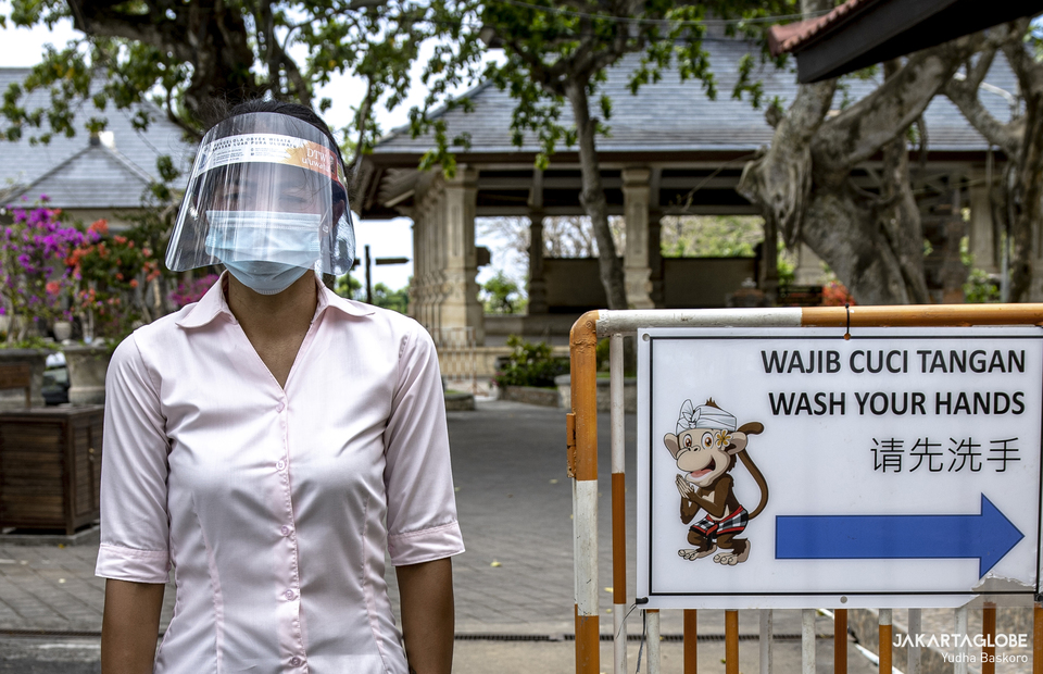 A woman wearing protective gear stands outside Pura Luhur Uluwatu in Bali on Tuesday (20/10). (JG Photo/Yudha Baskoro)