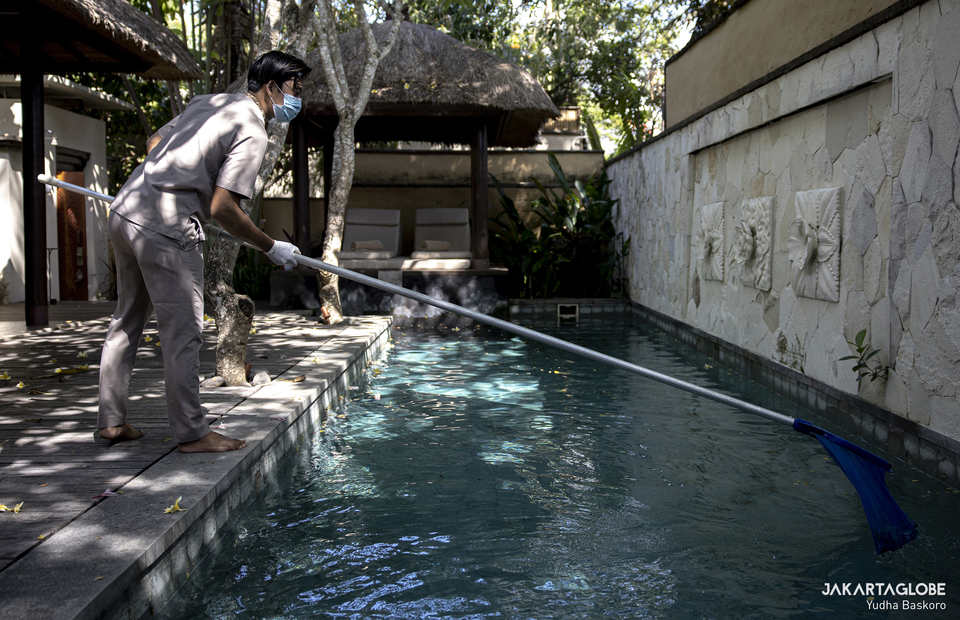 A hotel staff cleans a water pool inside Amarterra Villas Bali in Nusa Dua on Wednesday (21/10). (JG Photo/Yudha Baskoro)