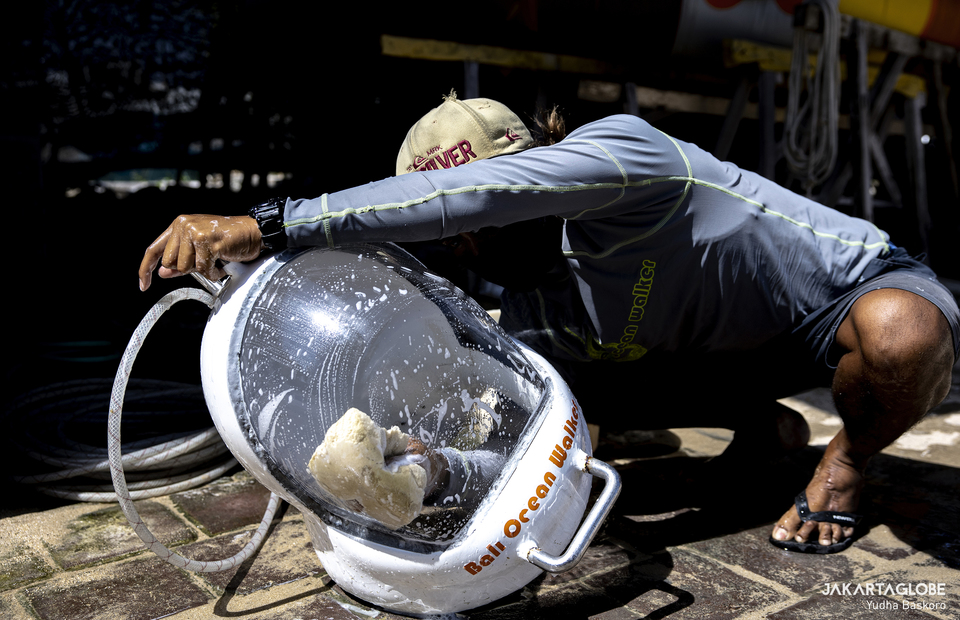 A man cleans a sea walker helmet in BMR Dive & Watersport in Tanjung Benoa, Bali on Tuesday (20/10). BMR Dive & Watersport has passed the Ministry of Tourism and Creative Economy (Kemenparekraf) CHSE-based health protocol certification (clean, healty, safety, environment). (JG Photo/Yudha Baskoro)