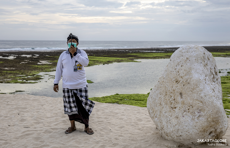 Made Suka Arjana, 45, a pecalang in Melasti Beach, stand on guard while maintaining health protocol guideline on the beach on Monday (19/10). (JG Photo/Yudha Baskoro)