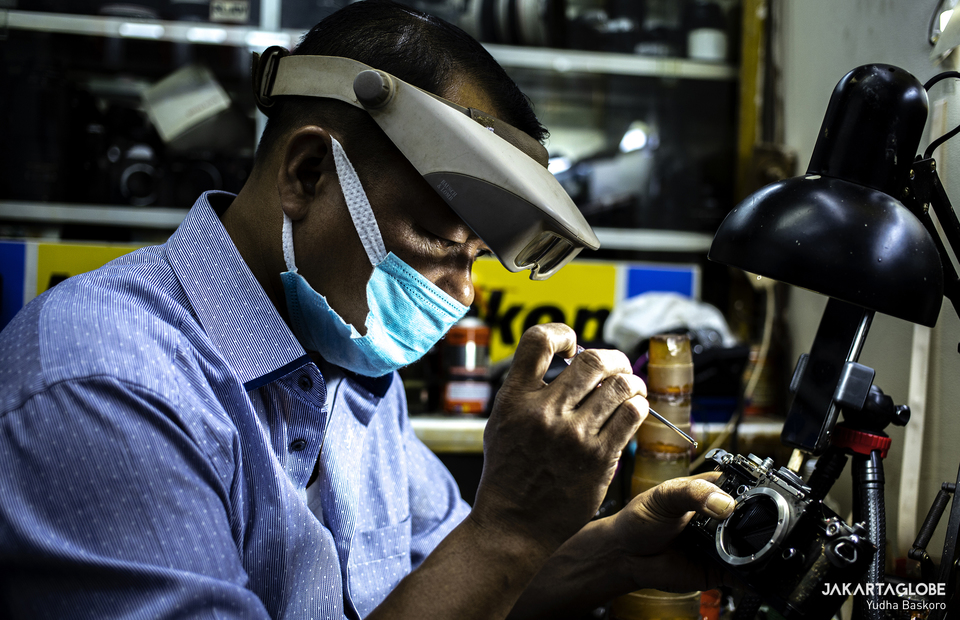 Rudy wearing health mask and zoom vision glass as he repairs an analog camera in Harco building in Pasar Baru area in Central Jakarta. (JG Photo/Yudha Baskoro)