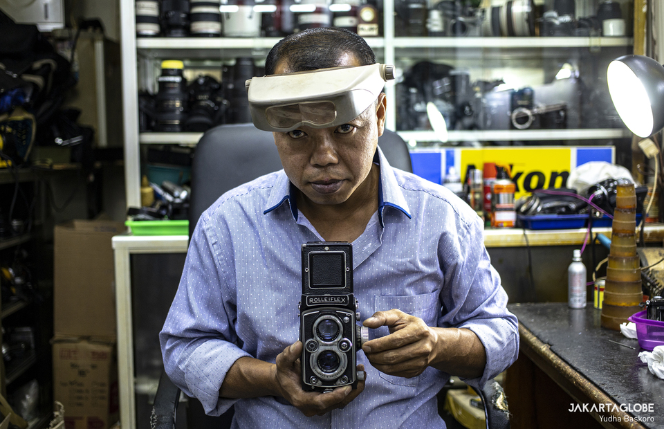 Rudy wearing zoom vision glass carries a medium format analog camera at his work station in Harco building, Pasar Baru in Central Jakarta. (JG Photo/Yudha Baskoro)