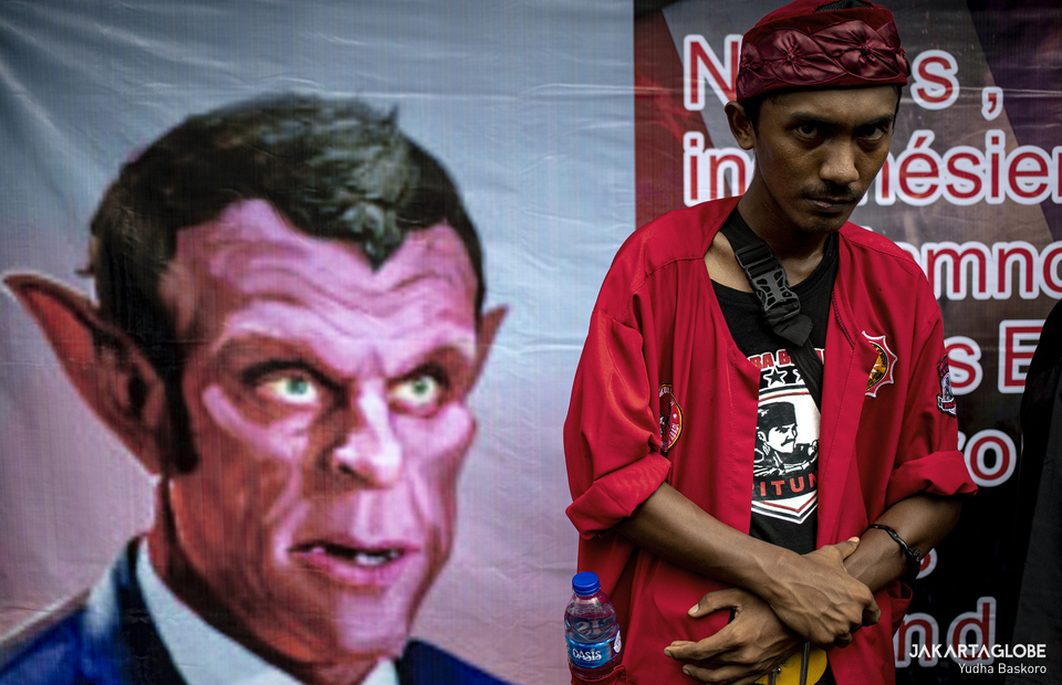 A protester stands beside a caricature of French President Emmanuel Macron during protest in front of French Embassy in Central Jakarta on Monday (02/11). (JG Photo/Yudha Baskoro)