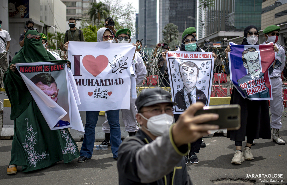 Protester takes a selfie during protest in front of French Embassy in Central Jakarta on Monday (02/11). (JG Photo/Yudha Baskoro)