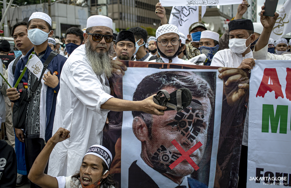 Protester puts his sandal on a poster with photo of Frens President Emmanuel Macron during protest in front of French Embassy in Central Jakarta on Monday (02/11). (JG Photo/Yudha Baskoro)