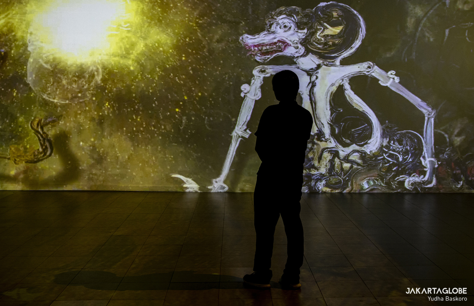 A man enjoying Affandi paintings through a video mapping projection during