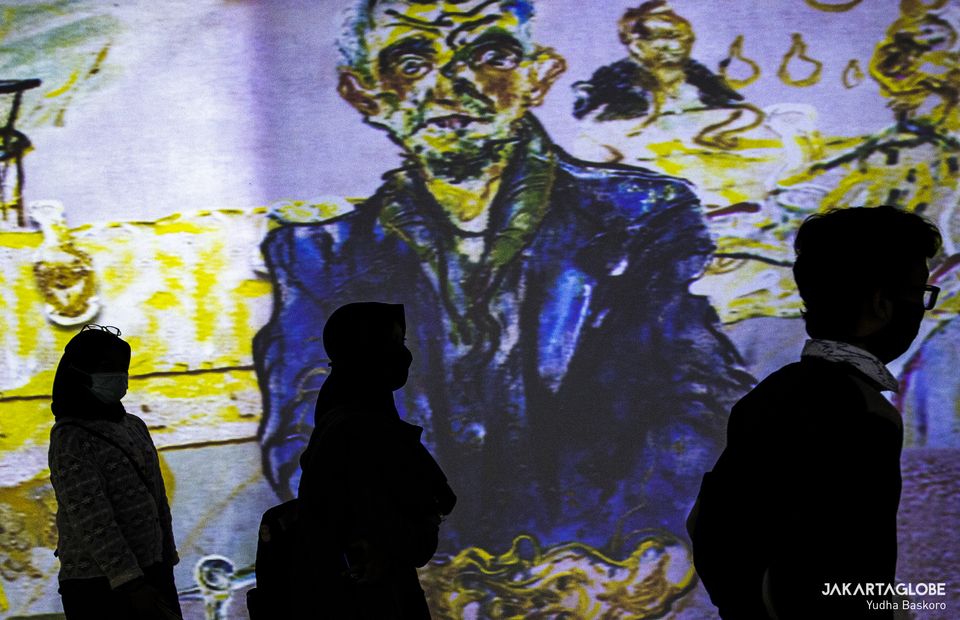 Visitors walks in front of Affandi paintings during