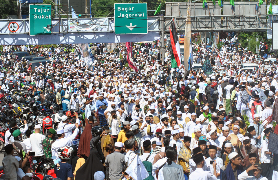 Thousands of people pack a road in Ciawi, Bogor, West Java, to welcome Islamic Defender Front (FPI) leader Rizieq Syihab on Nov. 13, 2020. (Antara Photo/Arif Firmansyah)
