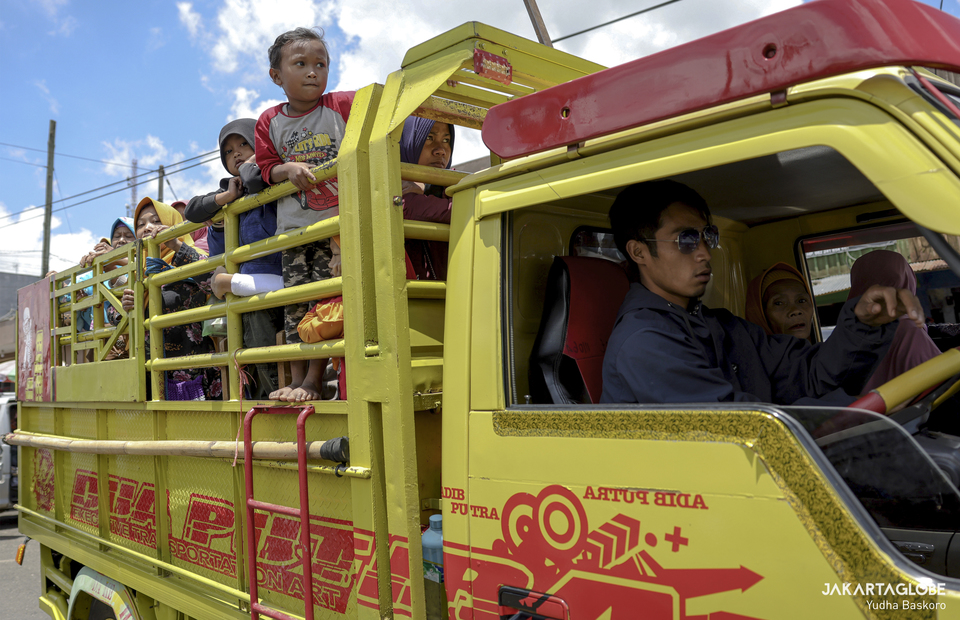 Dieng residents hop on a truck as they go to traditional market at Dieng plateau area in Banjarnegara, Central Java on Sunday (15/11). (JG Photo/Yudha Baskoro)