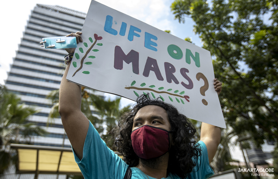A young activist carries a placard that reads Life On Mars during protest againts climate change in front of Jakarta City Hall on Friday (27/11). (JG Photo/Yudha Baskoro)