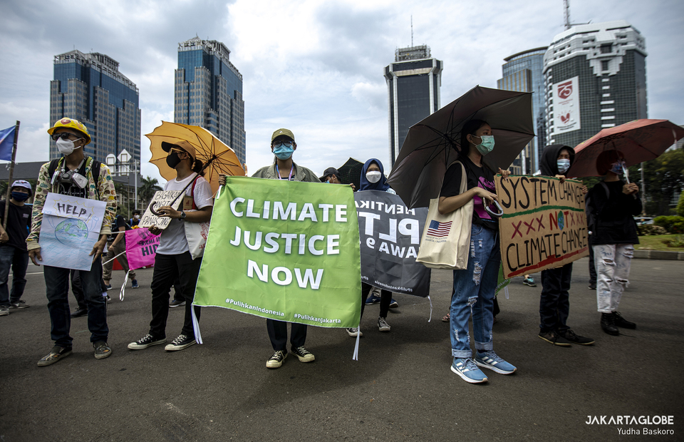 Climate activists gather in National Monument after long march on Friday (27/11). (JG Photo/Yudha Baskoro)