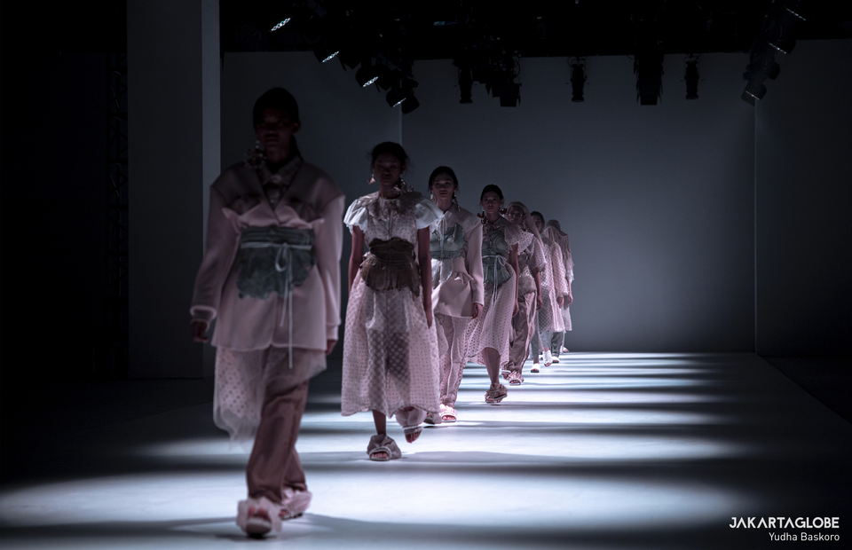 Models march on a catwalk during Jakarta Fashion Week 2021 on Sunday (29/12). (JG Photo/Yudha Baskoro)