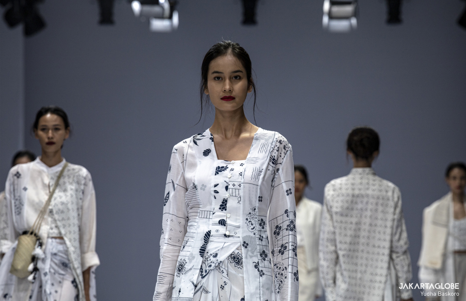 A model walks on a catwalk wearing Sejauh Mata Memandang collections during Jakarta Fashion Week 2021 on Sunday (29/12). (JG Photo/Yudha Baskoro)