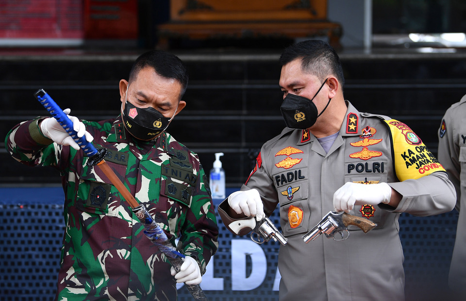 Jakarta Police Chief Insp. Gen. Fadil Imran, right, and Jakarta Military Command Chief Maj. Gen. Dudung Abdurachman, center, display weapons allegedly used by Islamic Defenders Front (FPI) members in an attack on police officers during a highway pursuit on Dec. 7, 2020. (Antara Photo/Sigid Kurniawan)