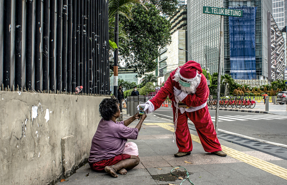 A man wearing Santa Claus costume gives a free coffee to a poor people at Central Jakarta on Friday (18/12). (Antara Photo/Aprillio Akbar)