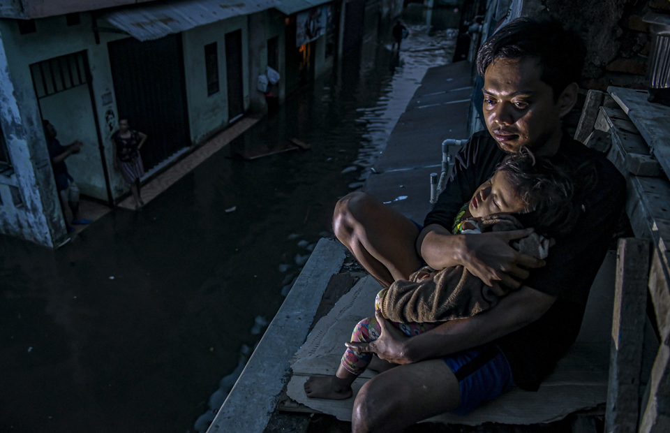 A resident of Kampung Baru in Kembangan, West Jakarta, comforts his child as water surrounds their house on January 3, 2020. The death toll from the New Year
