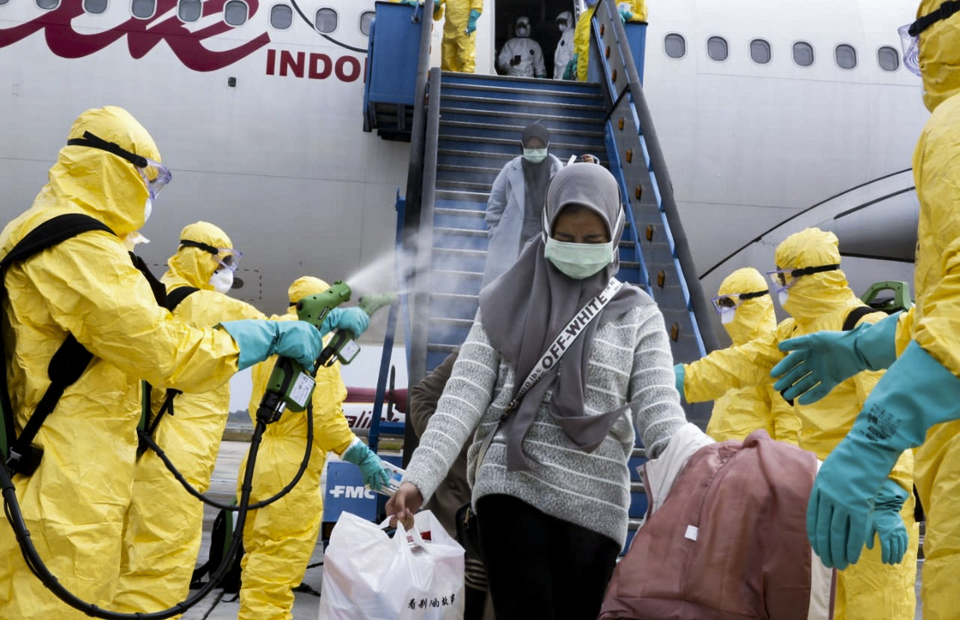 Medical staffs spray disinfectant at Indonesian passengers arriving from the Chinese city of Wuhan at the Hang Nadim Airport on Batam Island. The plane carrying the evacuees lands on the island on February 2, 2020. (Antara Photo)