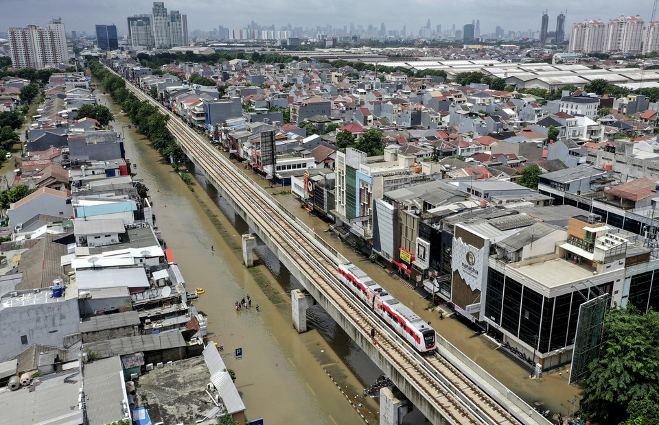 A Jakarta Light Rail Transit train passes over a flooded Jalan Boulevard Raya in Kelapa Gading, North Jakarta on February 23, 2020. Several hours of heavy rains on Sunday morning turned parts of Jakarta into muddy pools water for the second time this year after a major flood on New Year
