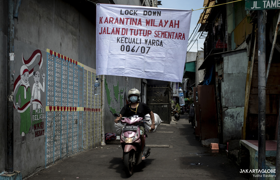 A man leaves Tambora on his scooter at Tambora, West Jakarta on April 1, 2020. Residents of Tambora, a subdistrict of West Jakarta with the highest population density in the capital, have enforced their own local lockdown to prevent the coronavirus from infecting their community.  (JG Photo/Yudha Baskoro)