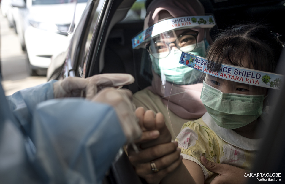 Health workers take a blood sample from a child through the window of a car during a drive-through rapid testing for coronavirus outside Lippo Mall Puri in West Jakarta on April 18, 2020. (JG Photo/Yudha Baskoro)
