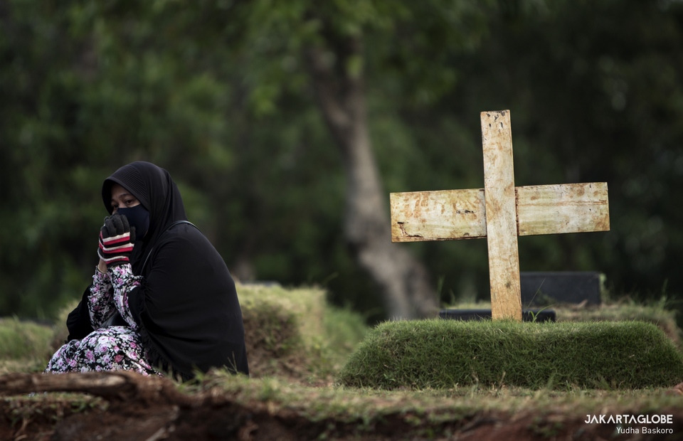 A woman prays next to a grave at the Pondok Ranggon public cemetery in East Jakarta - one of two public cemeteries designated for coronavirus victims in the capital - on April 22, 2020. (JG Photo/Yudha Baskoro)