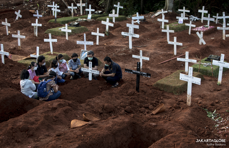 A family prays next to a recently filled grave at Pondok Ranggon. on April 22, 2020. (JG Photo/Yudha Baskoro)