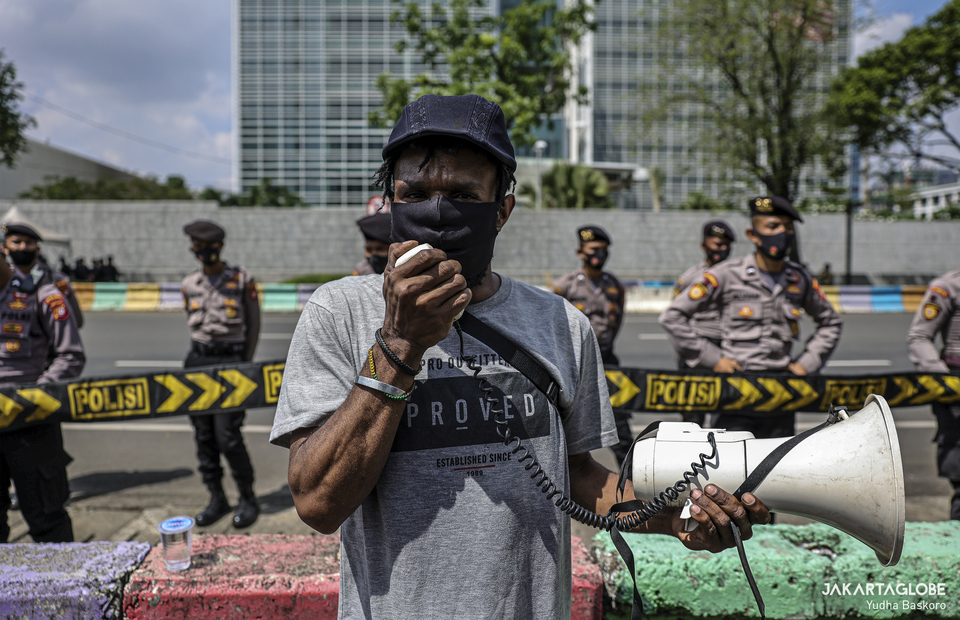 A Papuan activist delivers a speech as policemen stand guard in the background outside the US Embassy building in Central Jakarta. ctivists from the Indonesian People