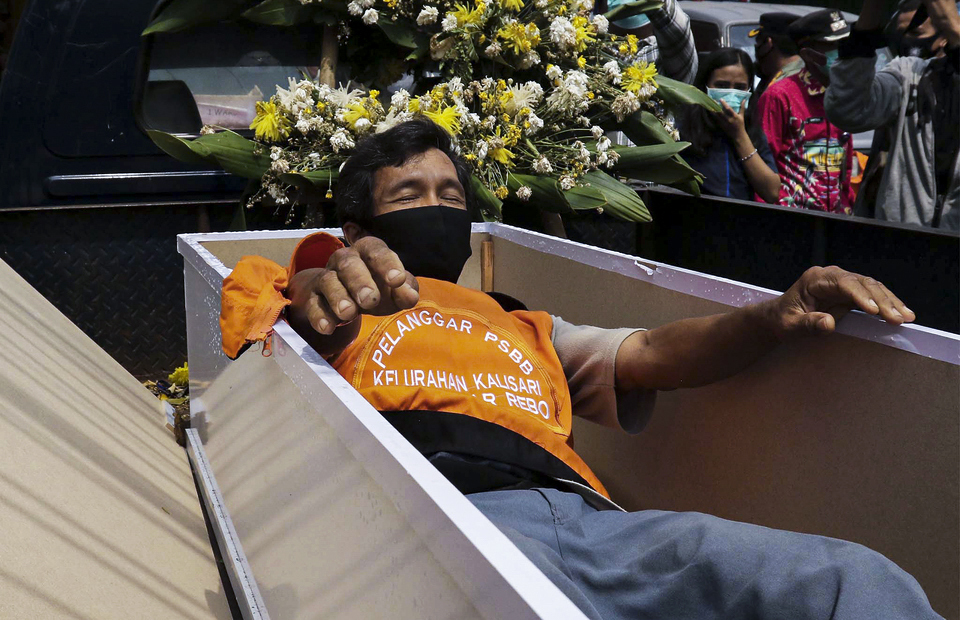 A man is ordered to lay in a coffin as punishment for not wearing a mask in Pasar Rebo, East Jakarta on Sept. 3, 2020. (Beritasatu Photo/Joanito De Saojoao)