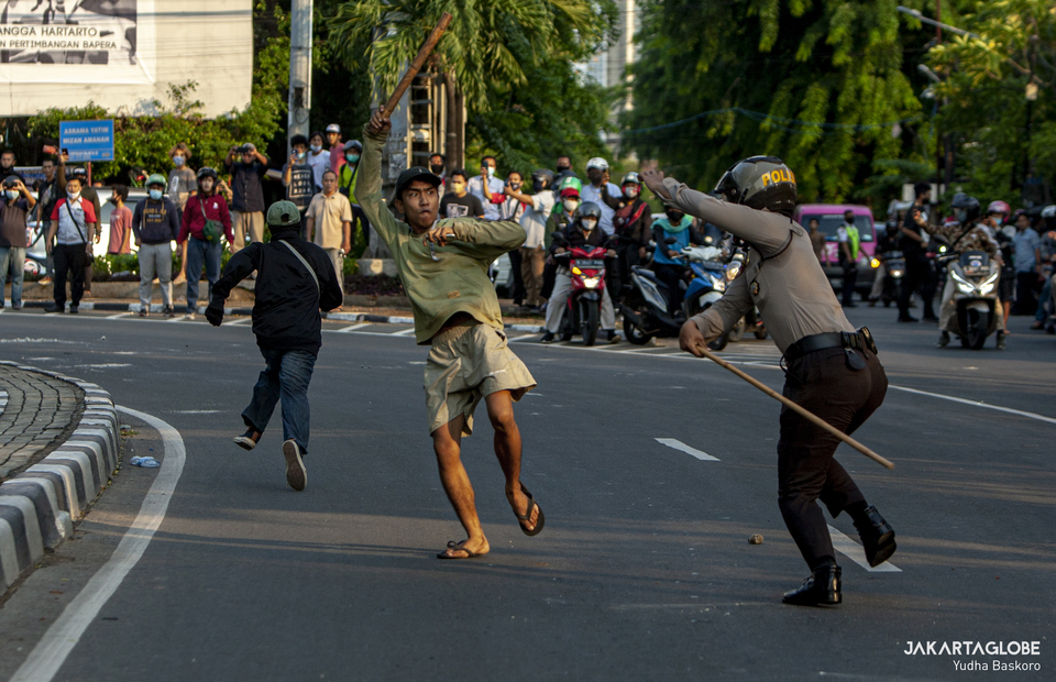 A rioter fights a policeman as a riot breaks out in Palmerah, West Jakarta on October 7, 2020. A riot has broken out in Jalan Pejompongan Raya, Palmerah, West Jakarta, on Wednesday, following a series of nationwide protests against the House of Representatives