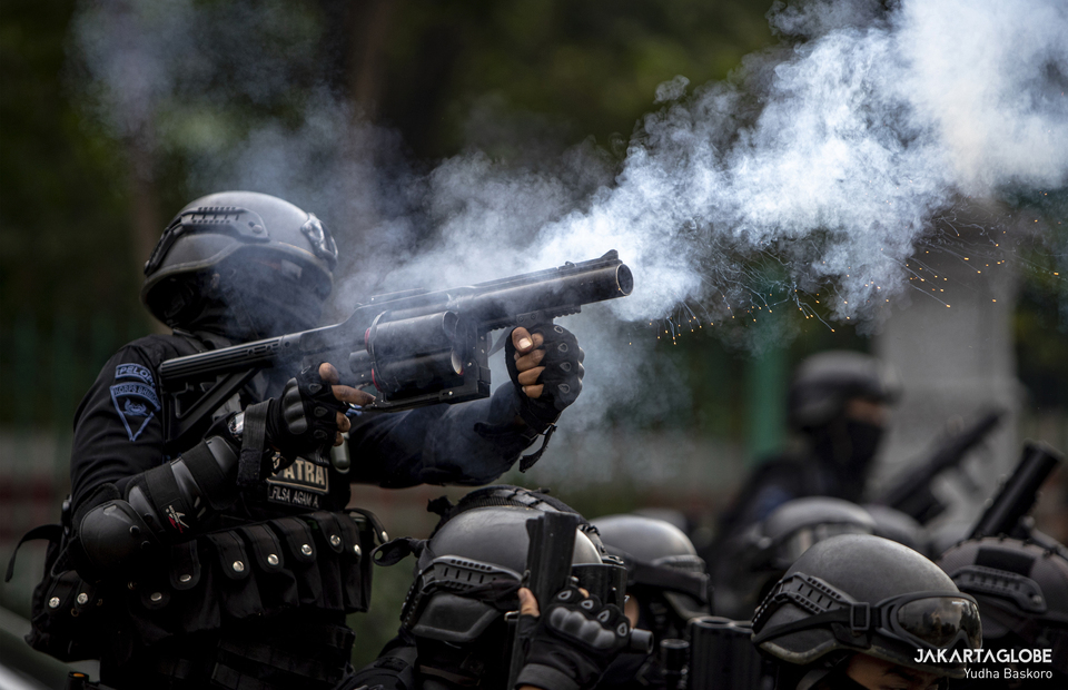 A police officer shots tear gas canister during a riot near Arjuna Wijaya Statue in Central Jakarta on October 13, 2020. A protest against Job Creation Law held by several Islamist hardline organizations in National Monument Complex has turned into a riot near the Arjuna Wijaya Statue roundabout in Central Jakarta. The Islamic Defenders Front (FPI) and the 212 Alumni Brotherhood (PA 212) started the protests peacefully at noon, and the protesters had told the police that they would disband at 04:00 p.m. But, as the protesters dispersed,  a group of teenagers ran towards the police barricade and showered the police with wood, bamboo, bricks, and bottles. (JG Photo/Yudha Baskoro)
