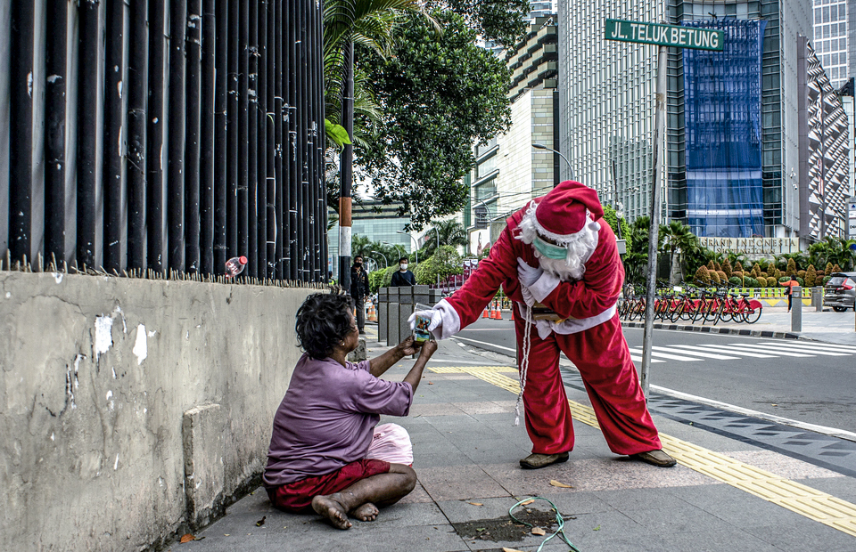 A man wearing a Santa Claus costume gives free coffee to poor people in Central Jakarta on December 18, 2020. (Antara Photo/Aprillio Akbar)