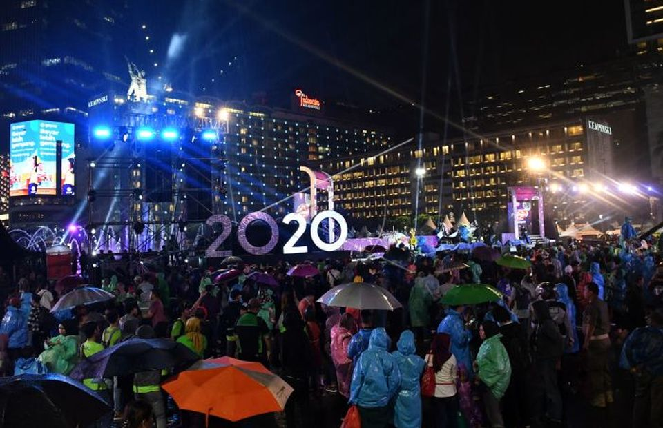 Jakarta resident wearing rain coat and umbrella enjoying car free day night during 2020 New Year Eve celebration at Hotel Indonesia Roundabout, in Central Jakarta on December 31, 2019. (Antara Photo/Aditya Pradana Putra)