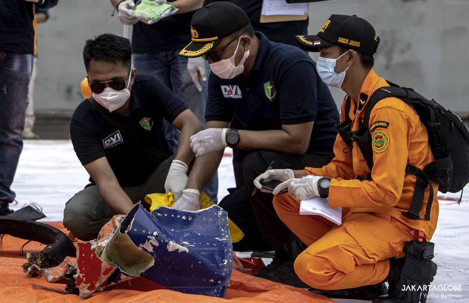 Police Disaster Victim Identification team at the Tanjung Priok post conduct an inspection to identified a collected debris and properties suspected coming from the Boeing 737-524 plane at JICT 2, Port of Tanjung Priok, in North Jakarta on Saturday (10/01). (JG Photo/Yudha Baskoro)